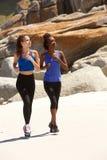 Mujeres jovenes que corren en la playa Imagenes de archivo