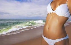 Mujeres jovenes que desgastan un bikiní en la playa fotografía de archivo libre de regalías