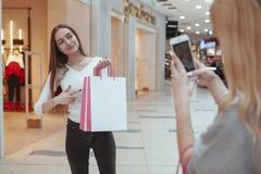 Mujeres jovenes que disfrutan de hacer compras junto en la alameda imagenes de archivo
