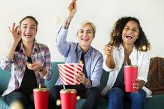 Mujeres jovenes que disfrutan de una película imagen de archivo
