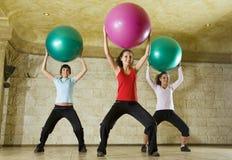 Mujeres jovenes que ejercitan con la bola de la aptitud Fotografía de archivo