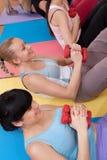 Mujeres jovenes que ejercitan con pesas de gimnasia Imagen de archivo