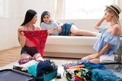 Mujeres jovenes que embalan las maletas para las vacaciones juntas en casa Imágenes de archivo libres de regalías