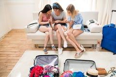 Mujeres jovenes que embalan las maletas para las vacaciones y que usan smartphones en casa, Imagenes de archivo