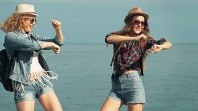 Mujeres jovenes que gozan y que bailan en una orilla de mar metrajes