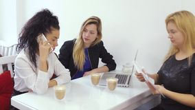Mujeres jovenes que hablan con el jefe en el teléfono que se sienta en la hora de la almuerzo en café metrajes