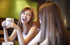 mujeres jovenes que hablan en cafetería Foto de archivo libre de regalías