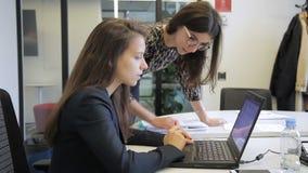Mujeres jovenes que hablan mientras que mira el ordenador portátil en oficina moderna metrajes