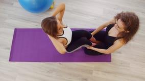 Mujeres jovenes que hacen aptitud en el estudio Una mujer que bombea su ABS que pone en la estera púrpura de la yoga mientras que almacen de metraje de vídeo