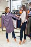 Mujeres jovenes que hacen compras y que miran un poco de ropa en una tienda Foto de archivo