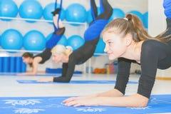 Mujeres jovenes que hacen ejercicio aéreo de la yoga o yoga antigravedad Fotografía de archivo libre de regalías