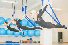 Mujeres jovenes que hacen ejercicio aéreo de la yoga o yoga antigravedad Fotos de archivo libres de regalías