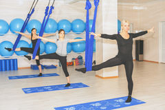 Mujeres jovenes que hacen ejercicio aéreo de la yoga o yoga antigravedad Fotografía de archivo