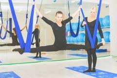 Mujeres jovenes que hacen ejercicio aéreo de la yoga o yoga antigravedad Imagen de archivo