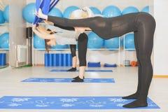 Mujeres jovenes que hacen ejercicio aéreo de la yoga o yoga antigravedad Fotos de archivo