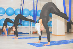 Mujeres jovenes que hacen ejercicio aéreo de la yoga o yoga antigravedad Foto de archivo