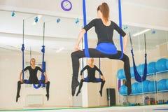 Mujeres jovenes que hacen ejercicio aéreo de la yoga o yoga antigravedad Foto de archivo libre de regalías