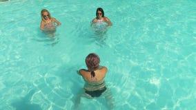 Mujeres jovenes que hacen el gimnasio de la aguamarina en la piscina del centro turístico en vacaciones almacen de video