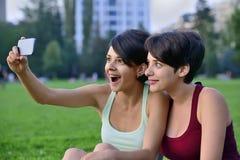 Mujeres jovenes que hacen la cara sorprendida mientras que mira el teléfono elegante Fotos de archivo