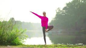 Mujeres jovenes que hacen la situación del ejercicio de la yoga metrajes