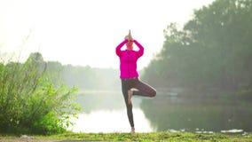 Mujeres jovenes que hacen la situación del ejercicio de la yoga almacen de metraje de vídeo