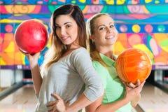 Mujeres jovenes que juegan a bolos y que se divierten Fotografía de archivo