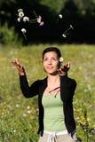 Mujeres jovenes que lanzan las flores en el aire Foto de archivo libre de regalías