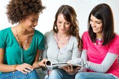 Mujeres jovenes que leen la revista Imagen de archivo libre de regalías