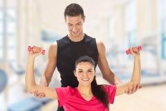 Mujer con su instructor personal de la aptitud que ejercita con los pesos en gimnasio imagenes de archivo