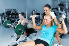 Mujeres jovenes que levantan una pesa de gimnasia con su amaestrador Imagen de archivo