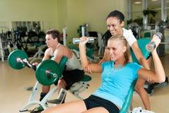 Mujeres jovenes que levantan una pesa de gimnasia con su amaestrador Imagenes de archivo