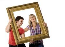 Mujeres jovenes que llevan a cabo el marco de madera foto de archivo libre de regalías