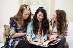 Mujeres jovenes que miran las revistas en un sofá Imagen de archivo libre de regalías