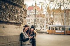 Mujeres jovenes que miran un teléfono móvil Fotografía de archivo libre de regalías