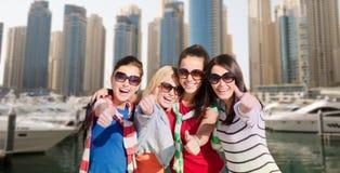 Mujeres jovenes que muestran los pulgares para arriba sobre puerto de la ciudad Foto de archivo libre de regalías