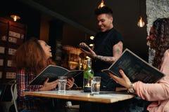 Mujeres jovenes que ponen orden a un camarero en el café Imagen de archivo