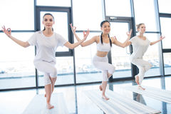 Mujeres jovenes que practican a Garudasana Eagle Pose en la clase de la yoga Fotos de archivo