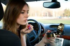 Mujeres jovenes que preparan su maquillaje en coche Foto de archivo libre de regalías