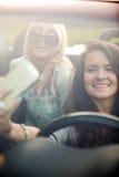Mujeres jovenes que presentan para el selfie en coche Foto de archivo