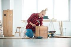 Mujeres jovenes que reparan los muebles en casa imágenes de archivo libres de regalías