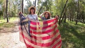 Mujeres jovenes que saltan y que sonríen con la bandera americana metrajes