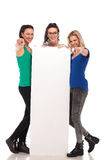 3 mujeres jovenes que señalan los fingeres mientras que lleva a cabo al tablero en blanco grande Fotografía de archivo libre de regalías