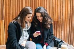 Mujeres jovenes que se divierten con un móvil Foto de archivo libre de regalías