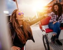 Mujeres jovenes que se divierten en dos triciclos Foto de archivo
