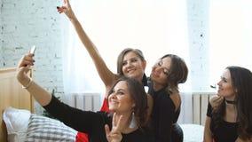 Mujeres jovenes que se divierten y que fotografían el selfie en partido del smartphone en casa almacen de video
