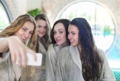 Mujeres jovenes que se relajan en el balneario que hace la toalla que lleva selfy Imagenes de archivo