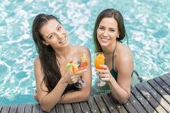 Mujeres jovenes que se relajan en la piscina Imagen de archivo