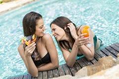 Mujeres jovenes que se relajan en la piscina Fotografía de archivo