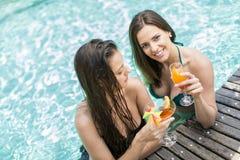 Mujeres jovenes que se relajan en la piscina Fotografía de archivo libre de regalías