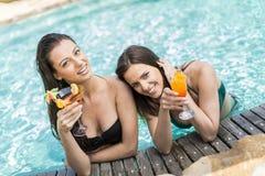 Mujeres jovenes que se relajan en la piscina Fotos de archivo